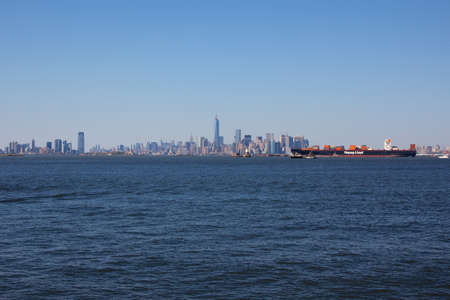 NEW YORK, NY, USA - MAY 27, 2013: Container freighter Yantian Express owned by German shipping company Hapag-Lloyd AG passes the New York City skyline on May 27, 2013 in New York, NY, USA. Editorial