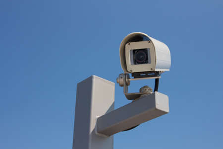 Security camera facing left before the background of a clear blue sky  photo
