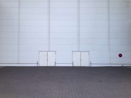 featureless: Vast space before a featureless gray wall with two doors. Stock Photo