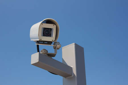 facing on the camera: Security camera facing right before the background of a clear blue sky