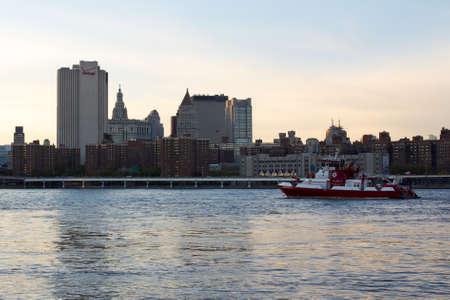 lower east side: NUEVA YORK, NY, EE.UU. - 13 de octubre 2012 Vista del barrio del Lower East Side de dos puentes en la oscuridad con un barco de FDNY en el East River en Nueva York, NY, EE.UU. en octubre de 2012 Editorial