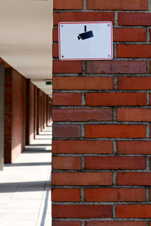 Sign with a camera pictograph warning of video surveillance on a red brick wall  photo