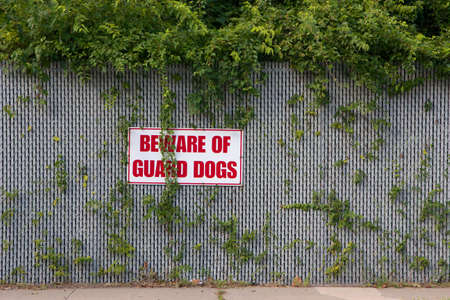Warning sign reading  Beware of Guard Dogs  mounted on an overgrown fence  photo