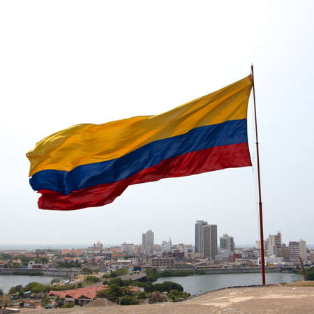 Colombian national flag streaming in the Caribbean winds above the old town of Cartagena de Indias, Colombia