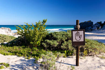 Keep out sign with hand pictograph at a Caribbean beach Stock Photo - 24469498