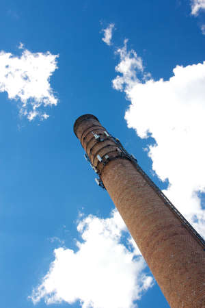 cel: Brick smoke stack with cel phone antennas rises into the blue sky before the camera