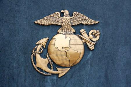 marine bird: TRI�NGULO, VA, EE.UU. - LATE 2010 Insignia de la Marina de los Estados Unidos en el metal bru�ido de oro en una pared azul-gris oscuro en el Museo de la Infanter�a de Marina en Triangle, VA, EE.UU., a finales de 2010