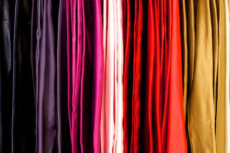 hangs: Cloth in many colors hangs from a rack at a store