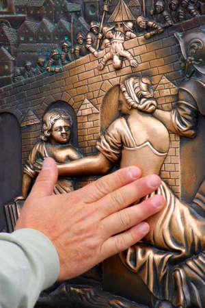 Tourist rubs bronze ornaments on the Charles Bridge for good luck in Prague, Czech Republic