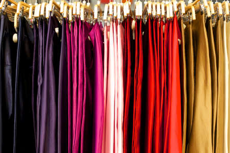 Skirts in many colors hanging on a clothes rack at a clothing store