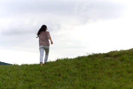 grassy knoll: Girl walks to the top of a grassy green hill under a dramatic overcast sky