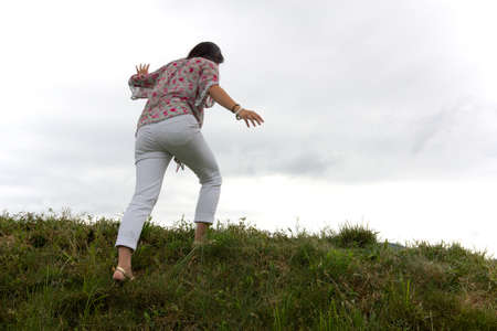 Wide-angle shot of girl topping grassy green ridge against a milky white sky