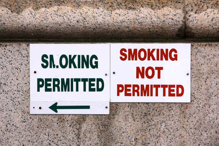 Two signs marking the border between the smoking and the non-smoking area outside a building  Stock Photo
