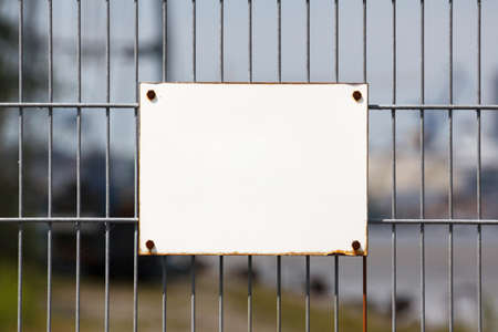 keep gate closed: Empty white sign on worn industrial fence offers copy space