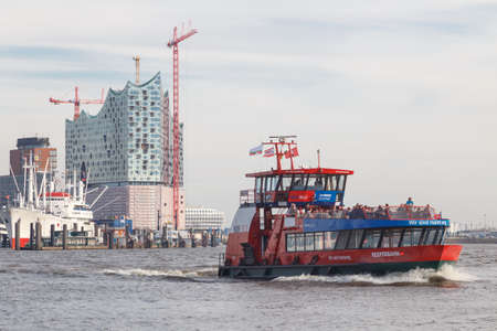 reeperbahn: HAMBURG, GERMANY - MARCH 20, 2014  Construction of the landmark Elbe Philharmonic building rises behind public harbor ferry  Reeperbahn   in Hamburg, Germany on March 20, 2014  Editorial