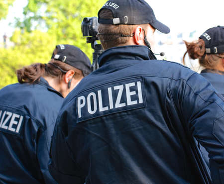 HAMBURG, GERMANY - MAY 1, 2021  Group of German police officers seen from behind wearing clothes marked  Polizei  during May Day protests in Hamburg, Germany on May 1, 2012  Editorial