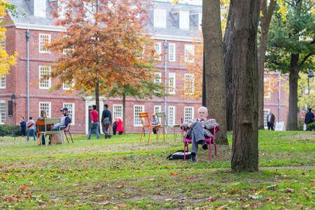 harvard university: CAMBRIDGE, MA, USA - NOVEMBER 2, 2013  Academic sits on lawn chair in Harvard Yard, old heart of Harvard University campus, and reads on a beautiful Fall day in Cambridge, MA, USA on November 2, 2013  Editorial
