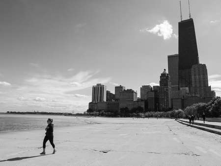 CHICAGO, IL, USA - OCTOBER 5, 2014: Woman runs along the beach of the Chicago Gold Coast with downtown skyscrapers in the background in Chicago, IL, USA on October 5 2014.