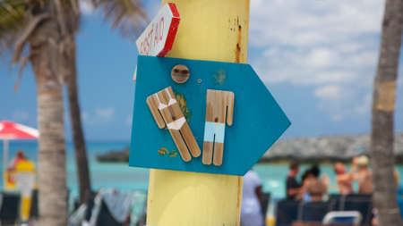 Damaged wooden sign on a crooked signpost pointing towards the restrooms at a Caribbean beach party. photo
