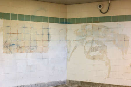 Grimy tiled wall at a subway station in the Southside of Chicago, IL, USA.
