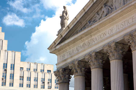 center court: New York State Supreme Court building in Lower Manhattan showing the words The True Administration of Justice on its facade in New York, NY, USA.