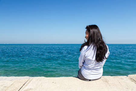 il: Young Asian woman sits at Lake Michigan in the Hyde Park area of Chicago, IL, USA on a sunny day.