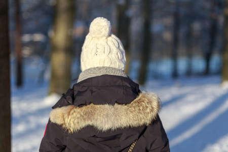 ropa de invierno: Detr�s de una mujer joven en ropa de invierno think como ella mira hacia un bosque cubierto de nieve.