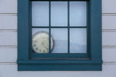 forgotten: An old clock lies forgotten behind a window. Stock Photo