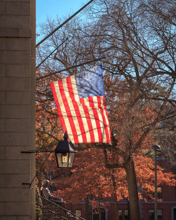 Backlit american flag over the John Harvard statue on a beautiful fall day in Cambridge, MA, USA.