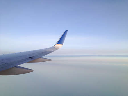 View from a jetliner of its right wing over creamy smooth clouds. photo