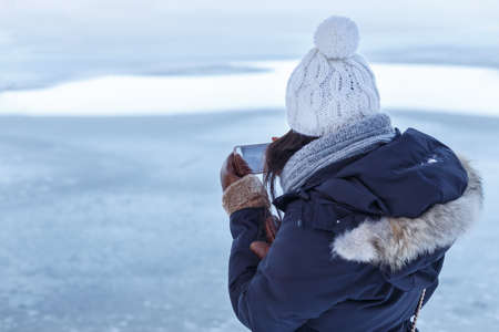 frozen lake: Young Asian woman in winter clothes seen from behind as she checks a photo on her smartphone in front of a frozen lake. Stock Photo