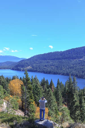 sierra nevada mountain range: Man takes photo of scenic Tahoe National Forest views on the California side of the Sierra Nevada.