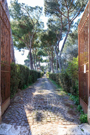 old buildings: Old gate leads to long path at the historic Via Appia in Rome, Italy. Stock Photo
