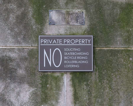 loitering: Private property sign annoncing the rules on a mossy limestone wall.