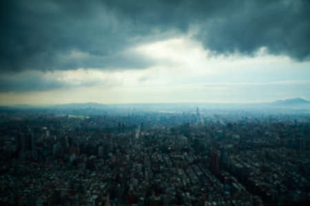 urban sprawl: Blurred background of aerial view of a city under dark clouds.