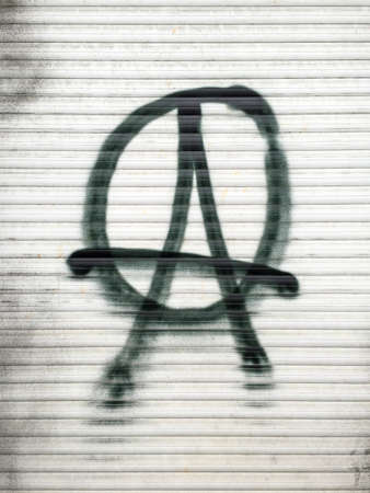 defaced: Anarchist symbol spray-painted on a shutter in Berlin, Germany.