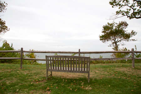 long island: Wooden bench on green grass overlooking the foggy Long Island Sound on Long Island, NY, USA. Stock Photo