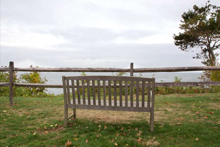 long island: Wooden bench on green grass overlooking the foggy Long Island Sound on Long Island, NY, USA. Stock Photo
