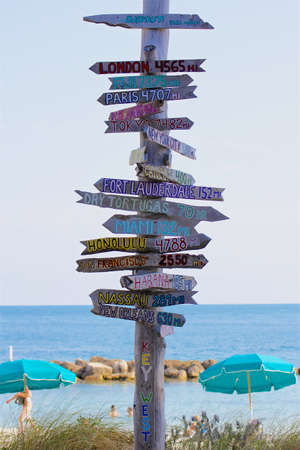 stating: A signpost at a Key West, Florida, beach pointing towards places around the world and stating their distance in miles.
