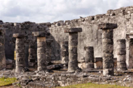 destination scenics: Blurred background of Mayan ruins with columns at the archeological site in Tulum, Quintana Roo, Mexico.