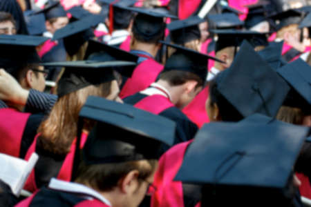 regalia: Blurred background of students in cap and gown at their graduation ceremonies. Stock Photo