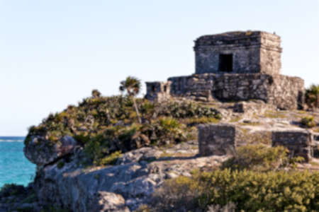 destination scenics: Blurred background of Mayan ruins perched on a cliff above the ocean at Tulum, Quintana Roo, Mexico. Stock Photo