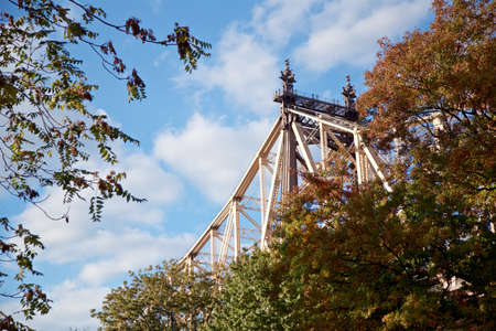 Tower of the 59th Street Bridge seen above the crowns of trees on Roosevelt Island, New York, NY, USA.