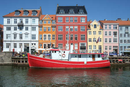 townhouses: COPENHAGEN, DENMARK - MAY 8, 2016: Canal in the historic harbor district of Nyhavn in Copenhagen, Denmark on May 8, 2016.