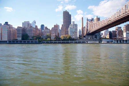 View of the Manhattan waterfront across the East River from Roosevelt Island, New York, NY, USA.