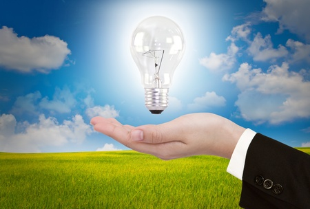 Business hand with Light bulb over blue sky Stock Photo - 10948920