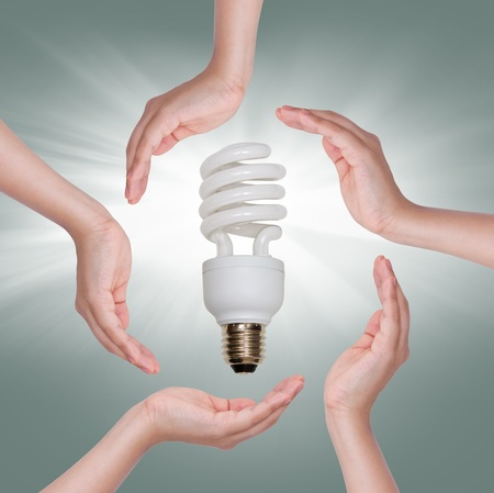 Energy saving fluorescent spiral light bulb in hand isolated on white background photo