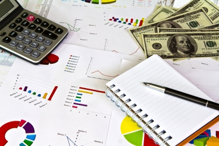 Pen ,calculator and dollars on financial Graphs photo