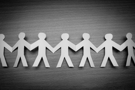 working together: Cutout paper people on wooden table