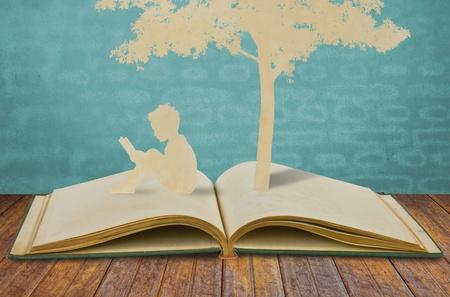 padres hablando con hijos: Cortar el papel de los ni�os a leer un libro bajo el �rbol